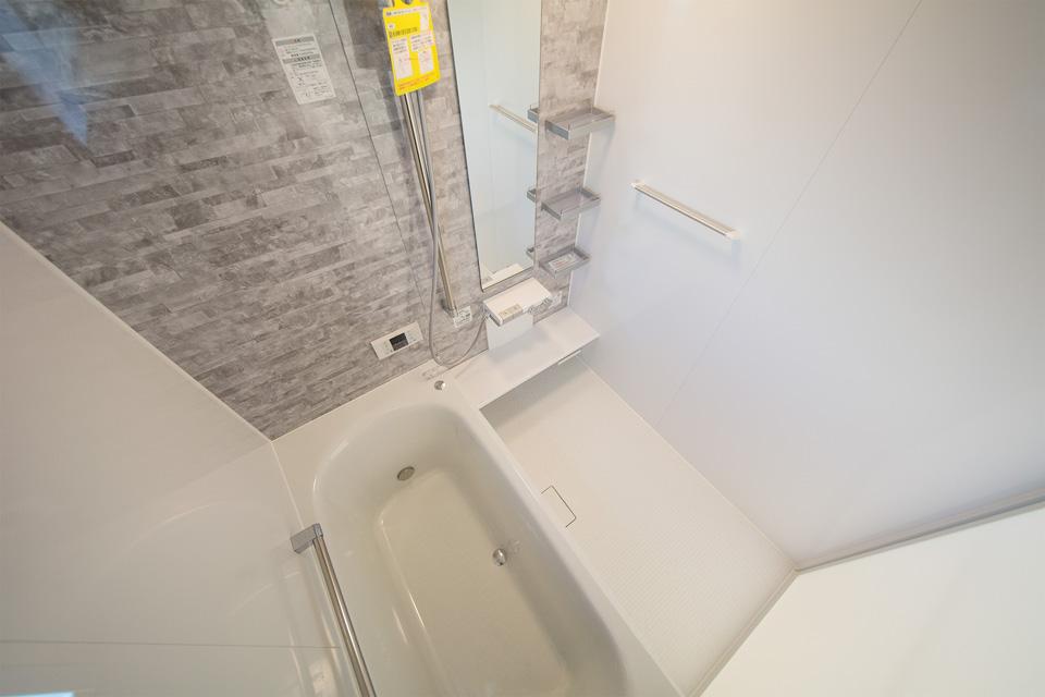 ライトグレーのアクセントパネルが明るく清潔感のあるバスルームを演出。