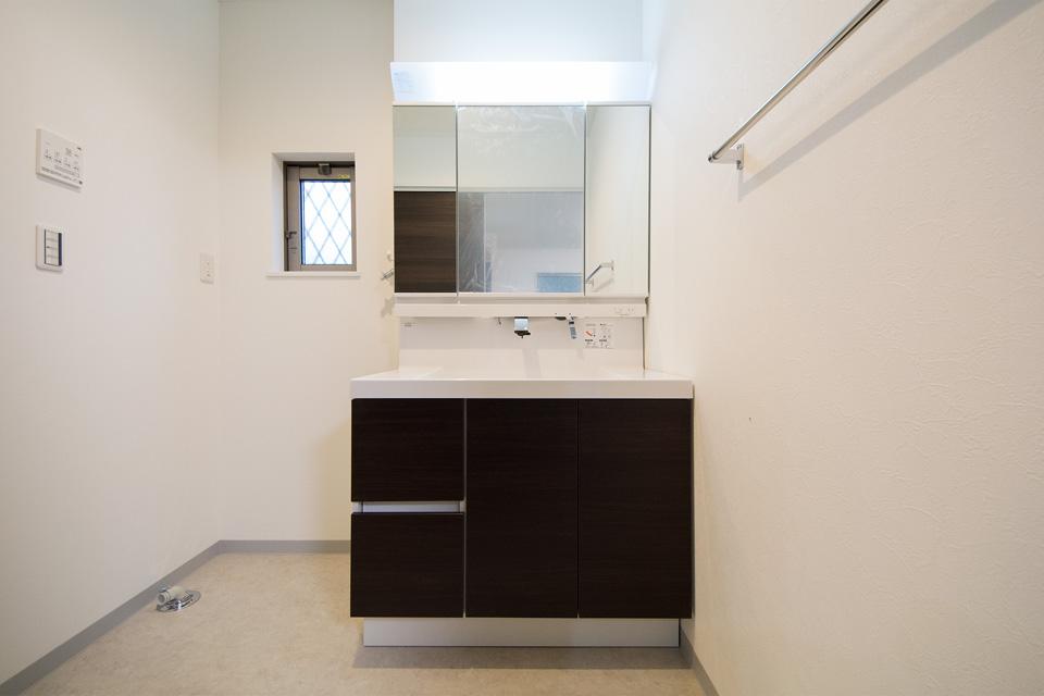 ダーク色の洗面化粧台が白いクロスを引き立たせ清潔感を演出。