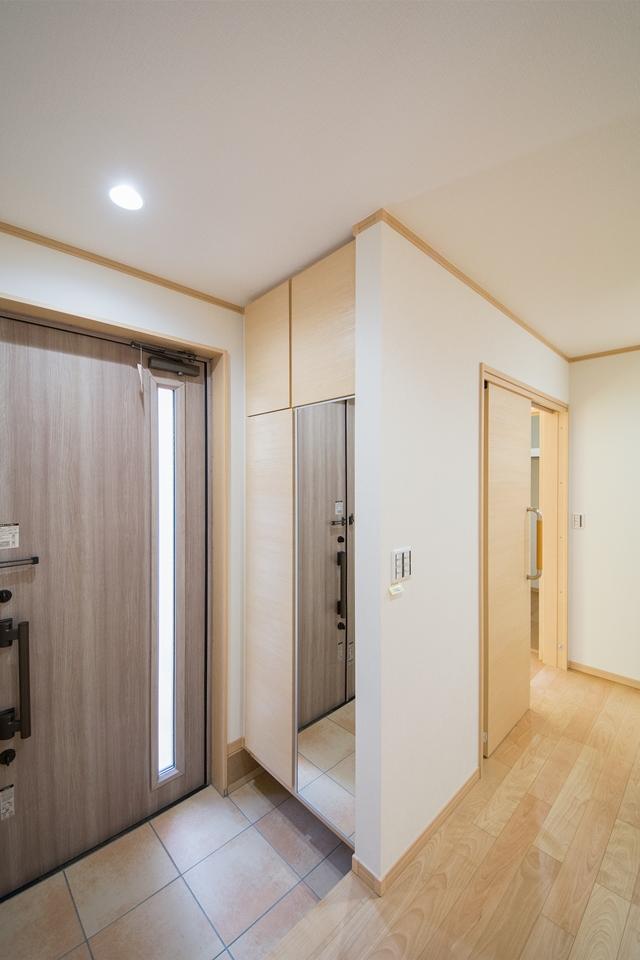 便利な全身鏡付き玄関収納を備えた明るい玄関。