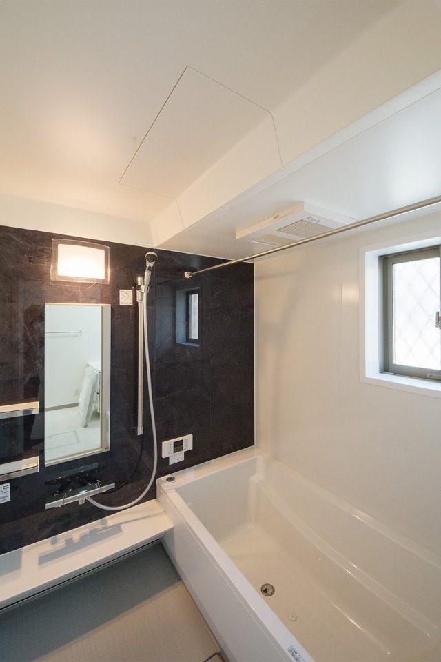 アクセントパネルにダークな色合いを配したバスルーム。
