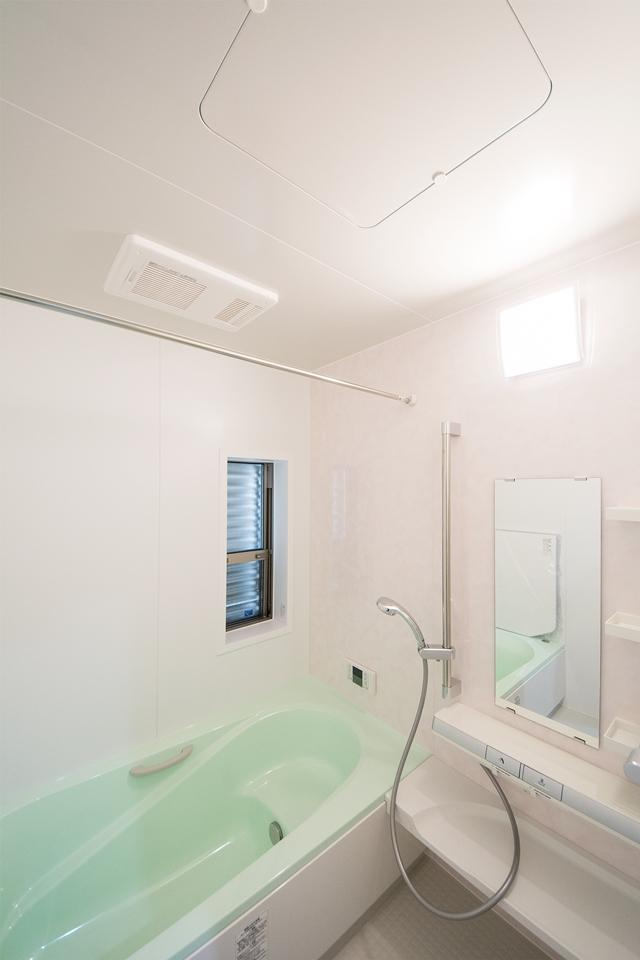 ライトグリーンの浴槽とライトピンクのアクセントパネルが明るく清潔感あるバスルームを演出。