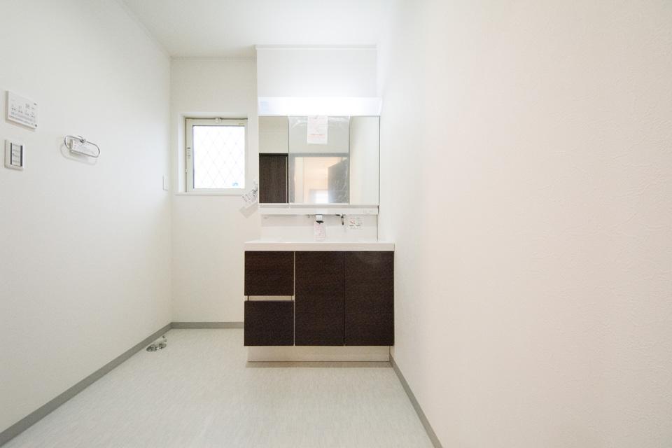 シンプルな配色が清潔感を感じさせるサニタリールーム。お手入れのしやすいビルトイン水栓。