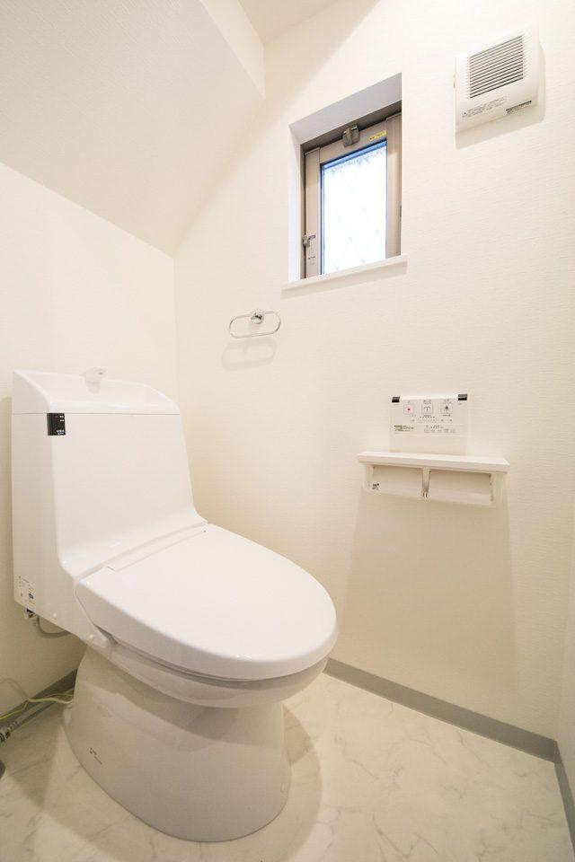 階段下のスペースを利用した1階トイレ。便利なリモコン付きシャワートイレ。