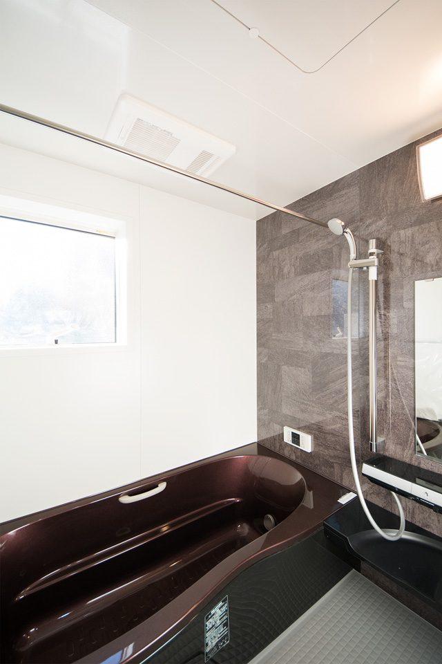 ゴールドブラウンの浴槽とブラウンのアクセントパネルがエレガントな雰囲気を演出。