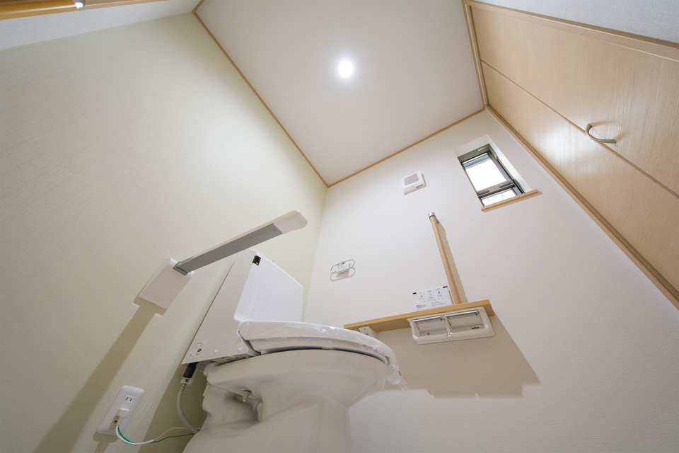 跳ね上げ式サポートレールを設置したトイレ。ライトグリーンのアクセントクロスでさわやかな空間に。