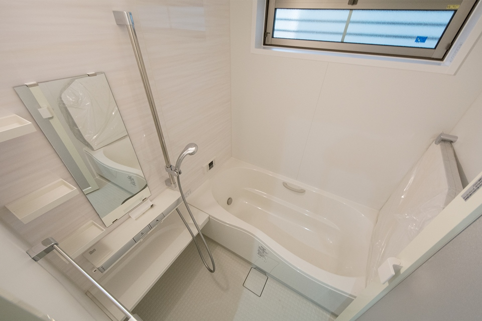 白を基調とした配色が清潔感を感じさせるバスルーム。指一本でお湯が出せるプッシュ水栓を使用。