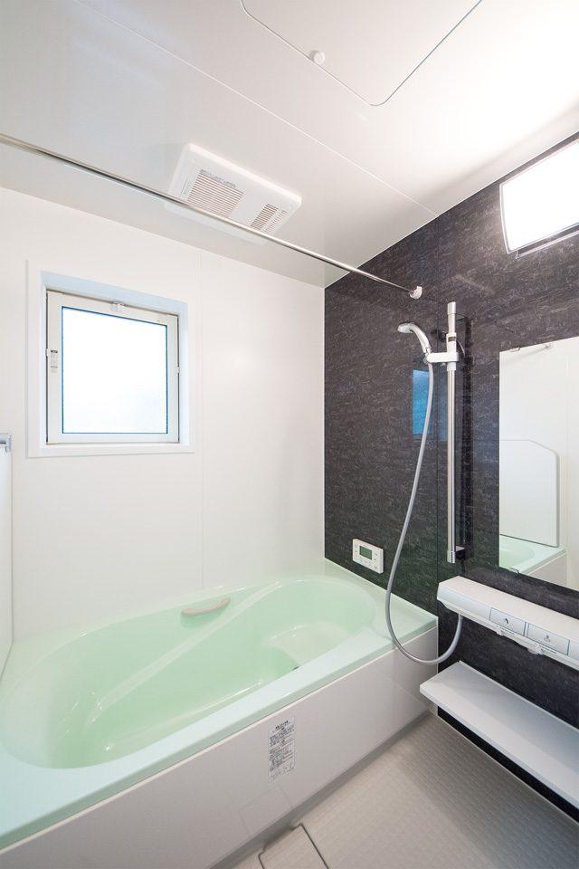 ダークなアクセントパネルとライトグリーンの浴槽が寛ぎのバスタイムを演出します。