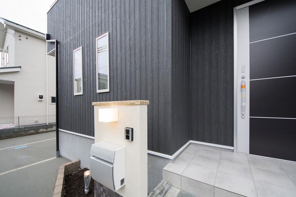 玄関ドアのアルミパネルと横ラインが黒い外壁になじみスタイリッシュさを演出。
