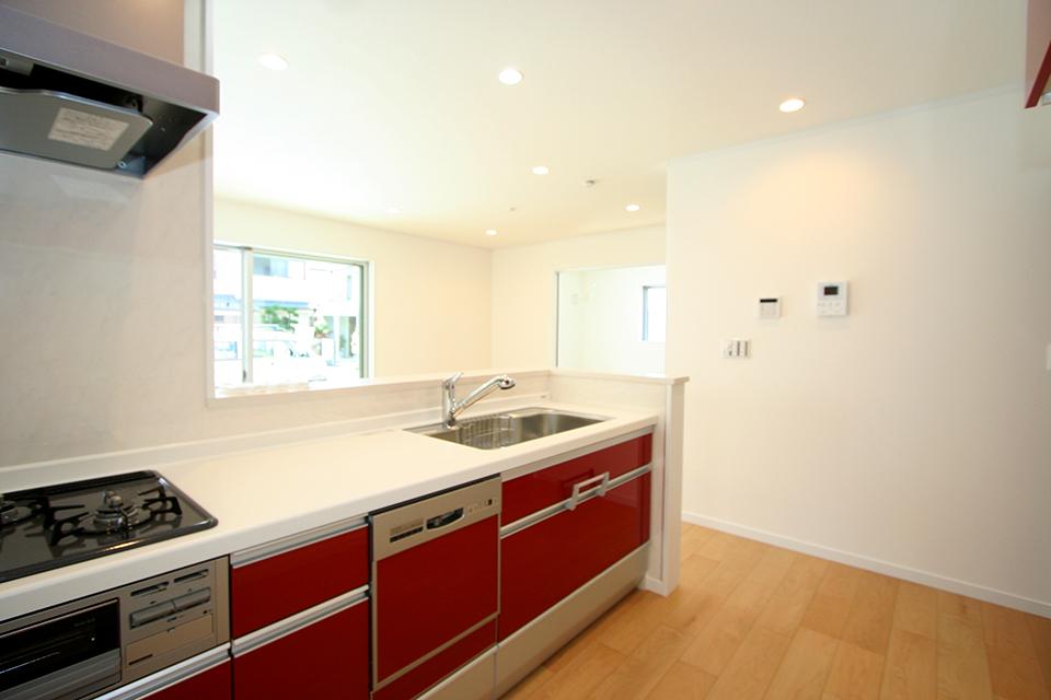 赤のキッチンがアクセントになっています