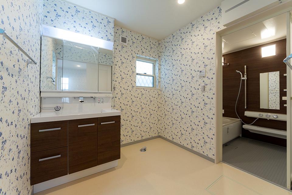かわいらしい青い小花模様の壁紙を貼った洗面室。