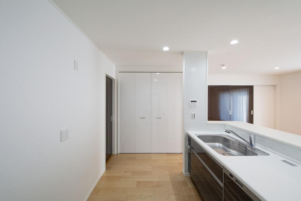 キッチン横には収納豊富なパントリーを設置。清潔感ある鏡面扉で仕上げました。