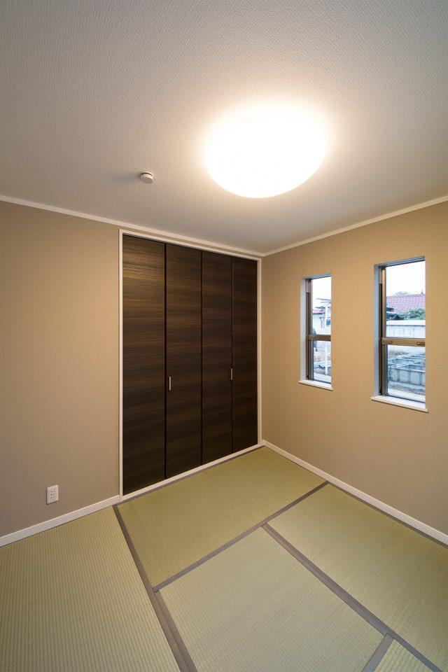 温かみのあるアクセントクロスを配した畳敷きの洋室