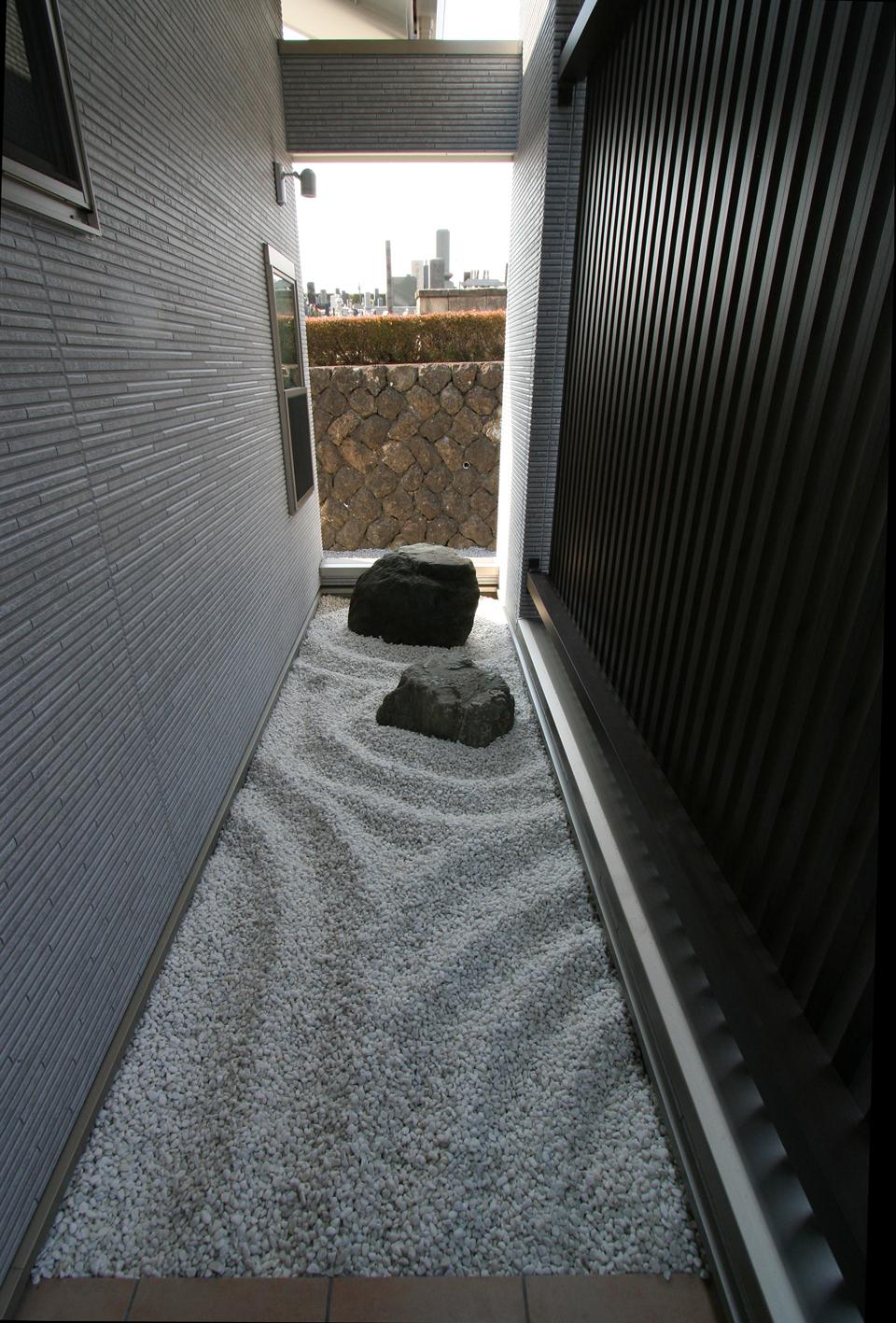 玄関ポーチから続く枯山水風の坪庭