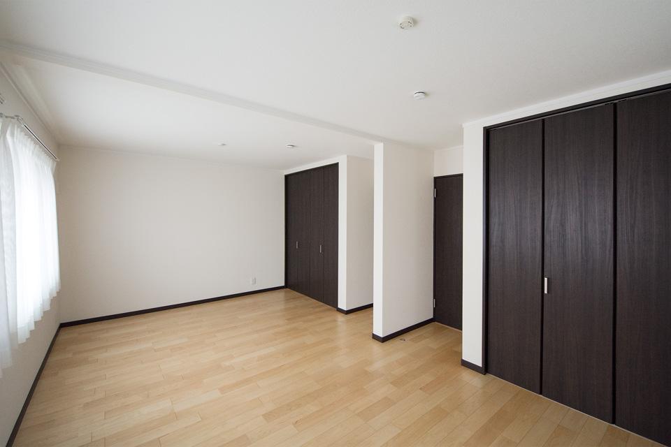 白のクロスとダークな色合いの建具が、木のやさしい風合いを感じる床となじみ、穏やかで寛ぎのある室内に。
