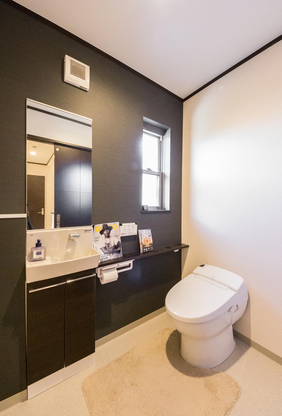 壁のアクセントクロスがシックなトイレ
