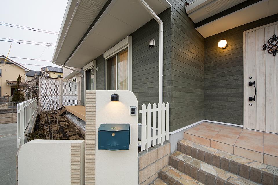 玄関ドアにはアイアンブラックの把手とオーナメントをしつらえ個性を主張。ウッドデッキのある庭ではガーデニングも楽しめます。
