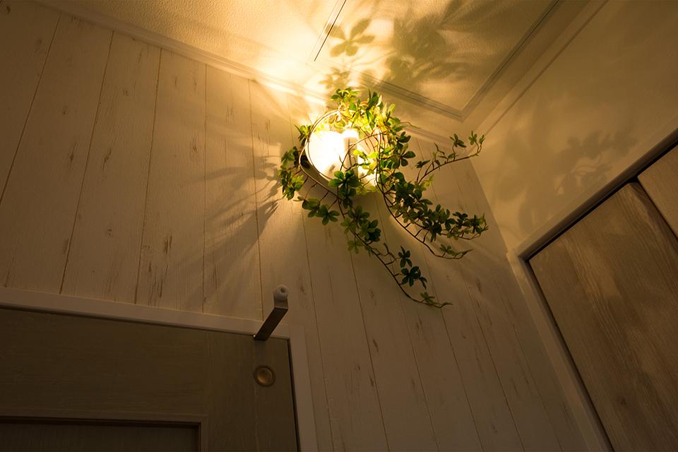 1階玄関ホールの雰囲気あるフェイクグリーン付LEDブラケットライト。