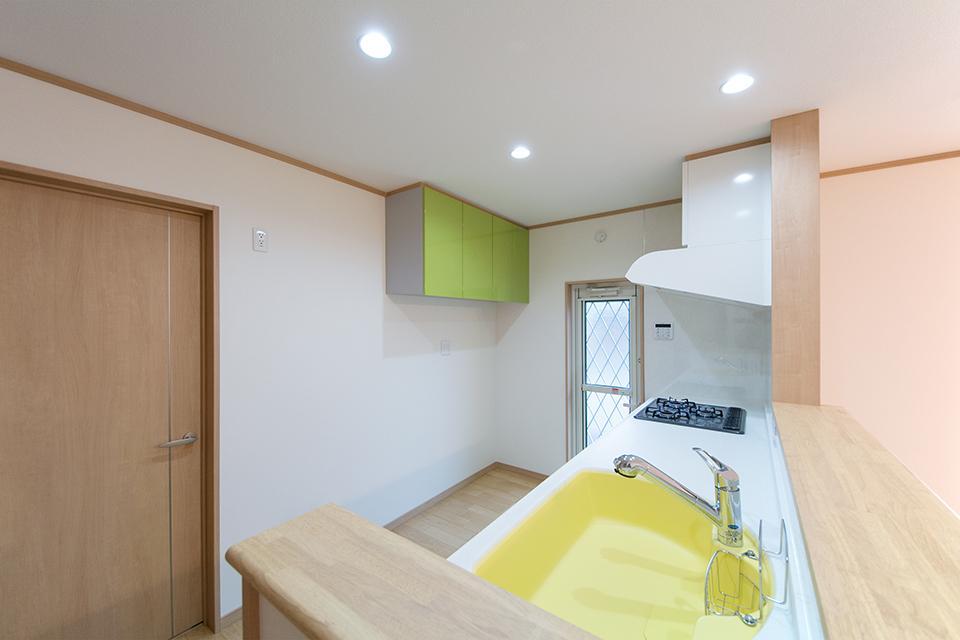 イエローのシンクと白のカウンターがキッチンスペースを明るく演出。