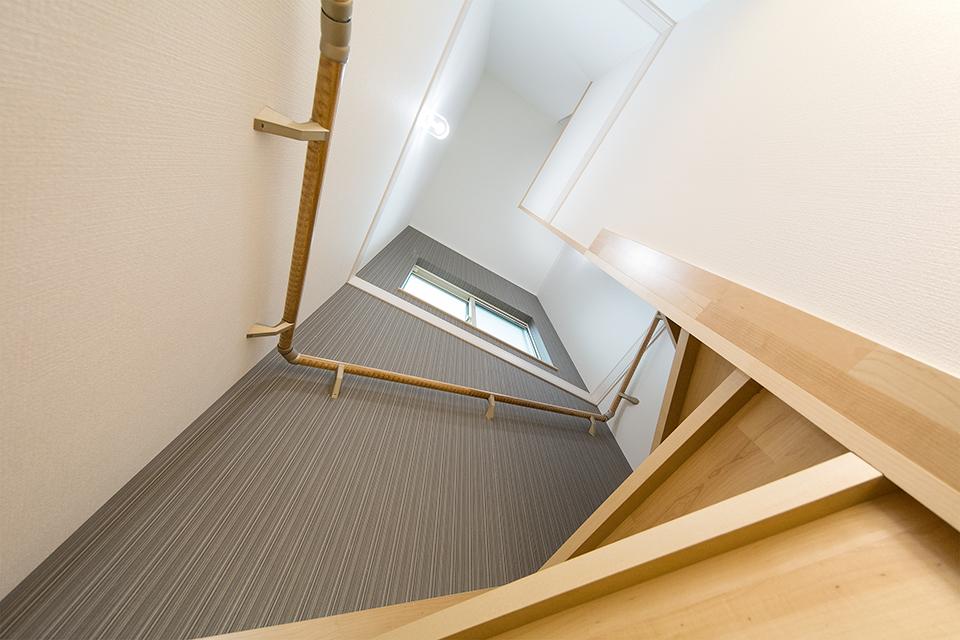 シックな色合いのアクセントクロスを使用した、開放感のある階段。