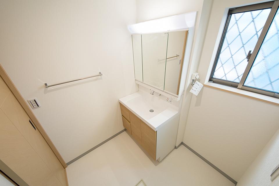 明るいメープル調の洗面化粧台と織物調の白いクロスが明るく清潔感ある洗面室を演出。