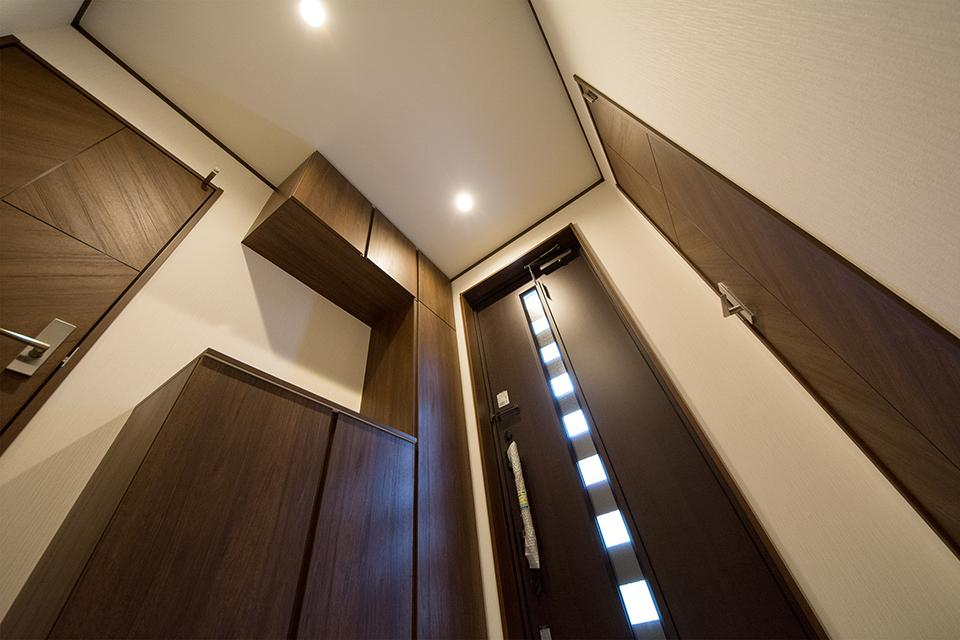 柿渋調の玄関ドアとダークブランの玄関収納が玄関スペースに深みを与えます。