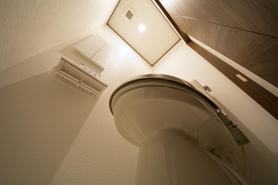 白を基調とし暖かみのある照明を使用した、落ち着く雰囲気のトイレ。