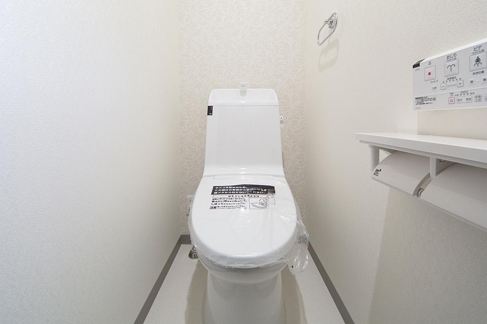 花の柄をモチーフにした白のクロスが、さり気なくエレガントに清潔感を演出する1階トイレ。