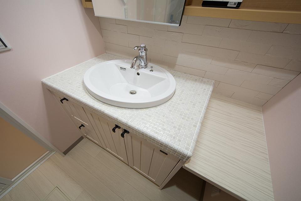 無垢の木の洗面台にオーバルボウルの洗面器、素朴な風合いのタイルカウンターがとってもお洒落。