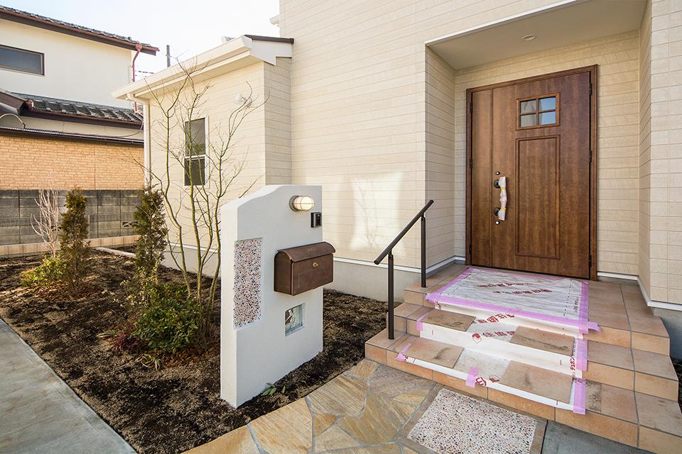 ダークブラウンの玄関ドアとアイアンブラックの把手、オレンジのタイルがアクセントとなりファサードを彩ります。