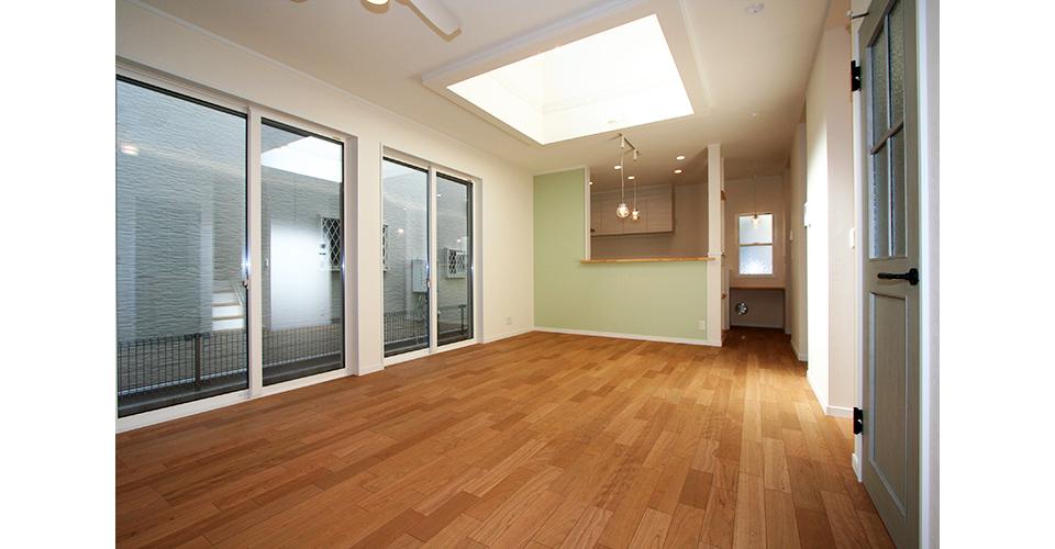 広いリビングはカウンターキッチンのグリーンの壁とブルーの扉がポイントです。