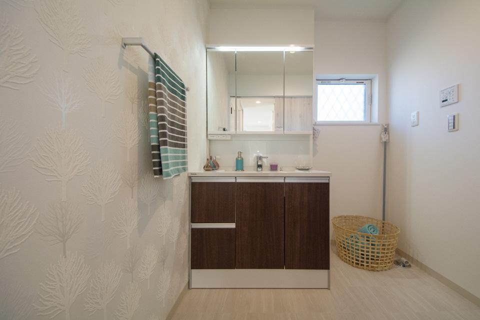 木をモチーフにしたアクセントクロスがダークブラウンの洗面化粧台とマッチした清潔感あるサニタリールーム