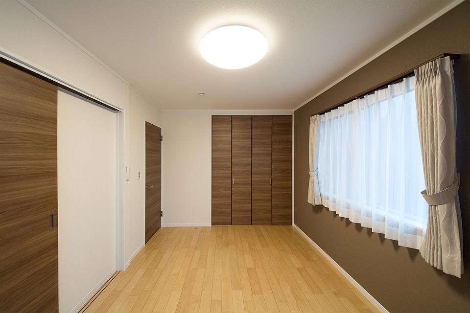 ブラウンのアクセントクロスを使用した洋室。シックで落ち着いた雰囲気を演出しています。