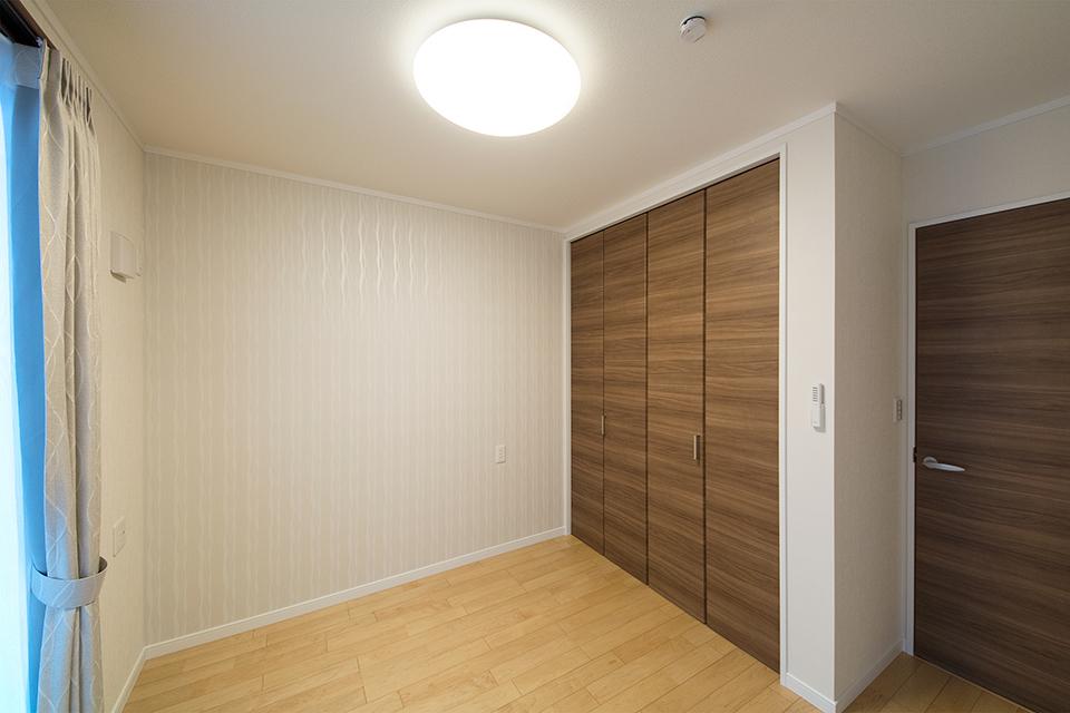 白のクロスとメープル色のフローリングが優しい雰囲気を演出する洋室。