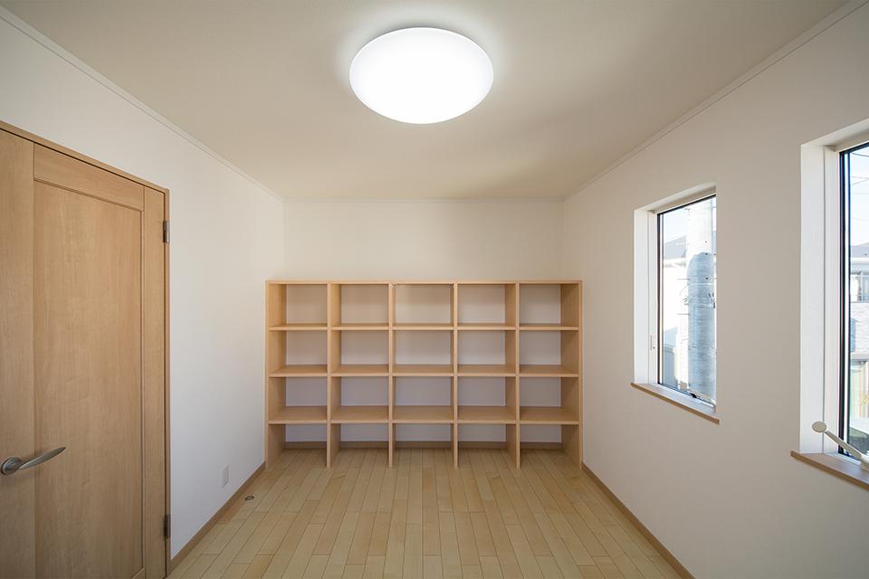 壁一面に造作本棚を設置した2階洋室。小物のディスプレイにも便利です。