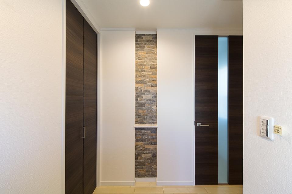 玄関正面に設えたニッチ棚。石目調のアクセントクロスが落ち着いた雰囲気を演出。