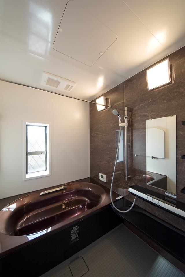 ゴールドブラウンの浴槽とシックなアクセントパネルを使用した、エレガントな雰囲気のバスルーム