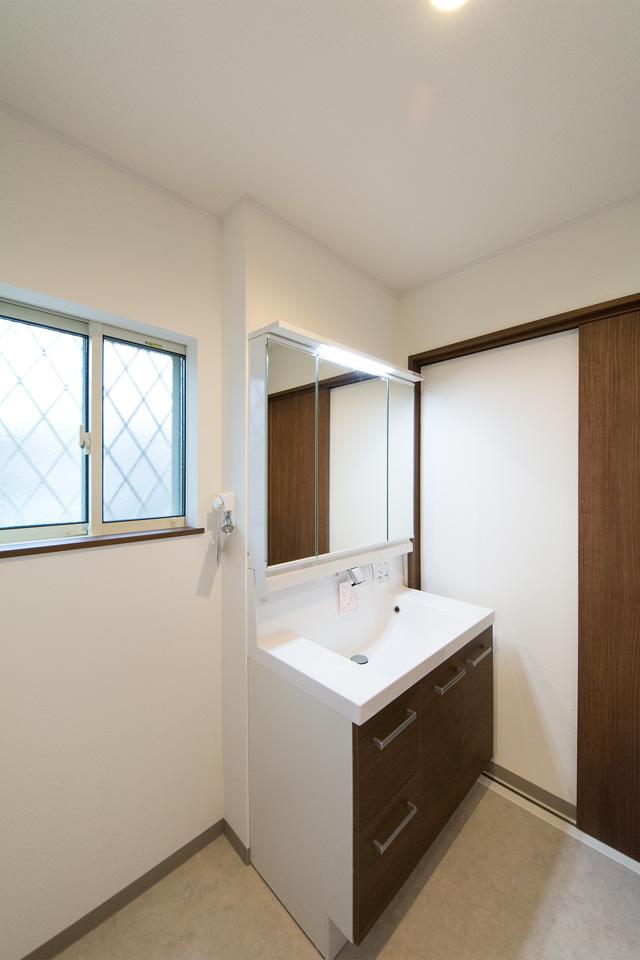 建具の色と合わせたダークブラウンの洗面化粧台。