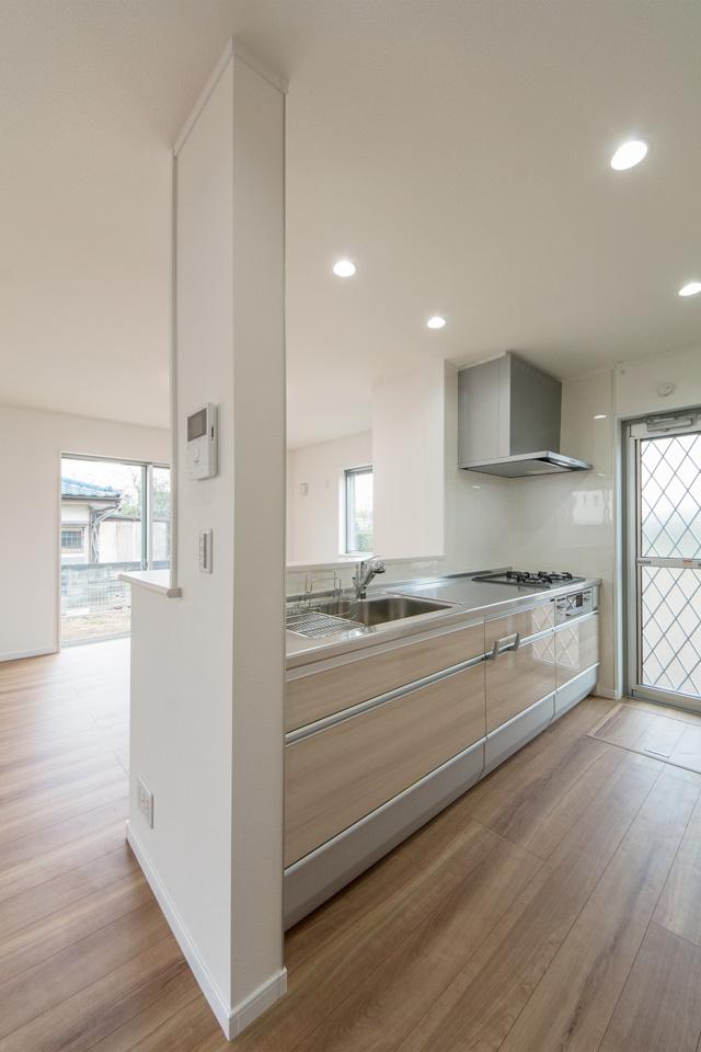 ナチュラル色の扉とコイニング柄のステンレスワークトップで、清潔感あるキッチンスペースに。