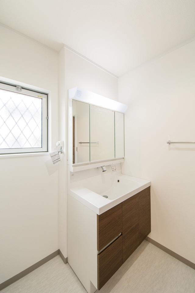 建具の色と合わせたブラウンの洗面化粧台。