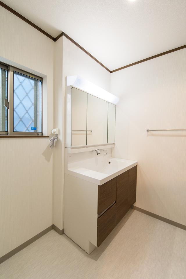 三面鏡とビルトインタイプの水栓を備えた洗面化粧台。モカカラーで建具との統一感を。