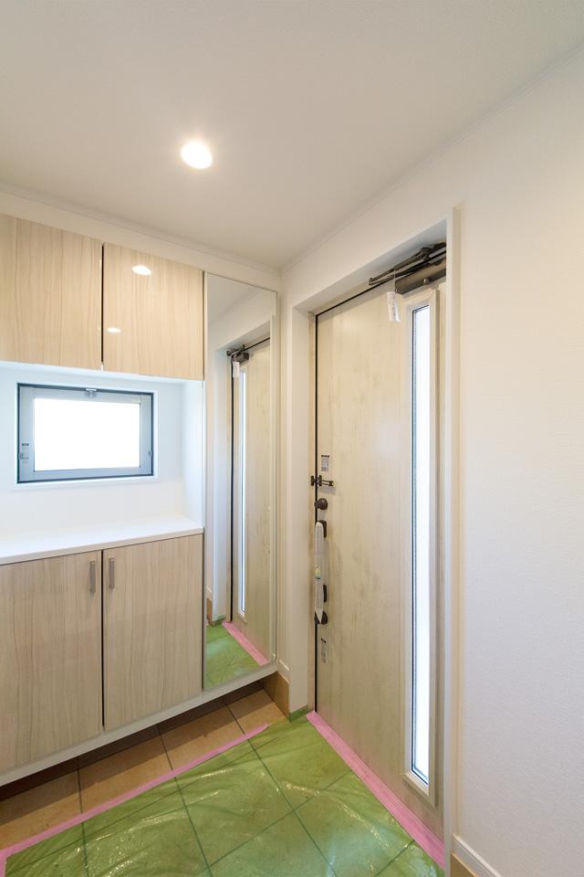 ドアとキャビネット背面から採光し、明るい玄関空間に。