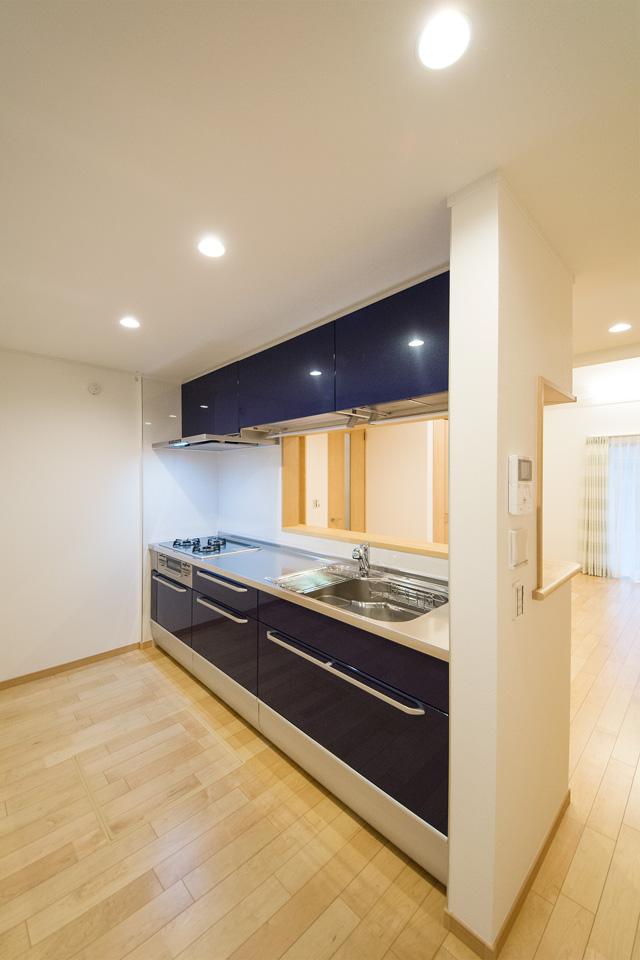 ルナブルーのキッチン扉とコイニング柄ステンレストップが印象的なキッチン。