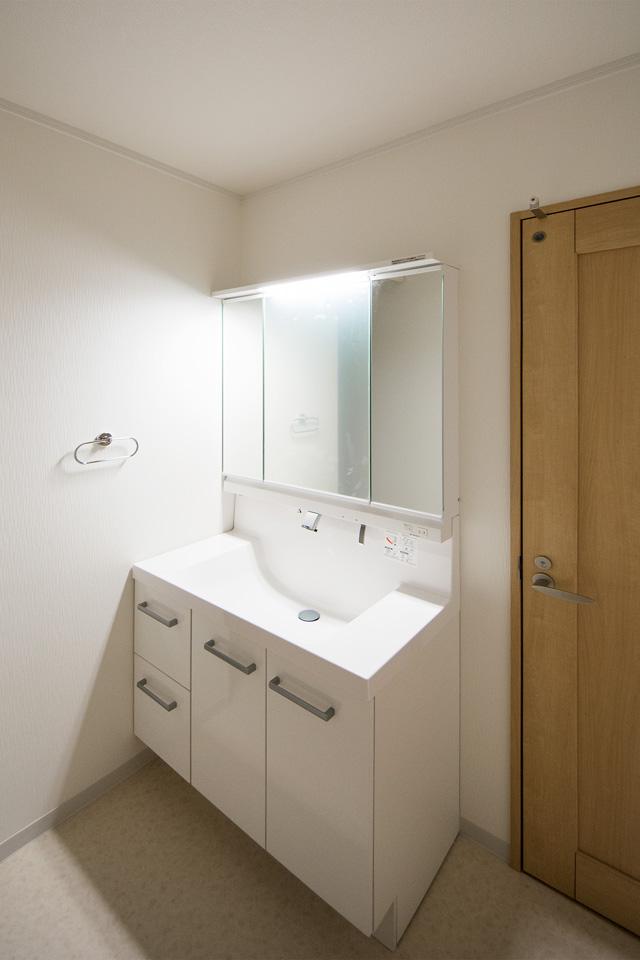 三面鏡とビルトインタイプの水栓を備えた便利な洗面化粧台。