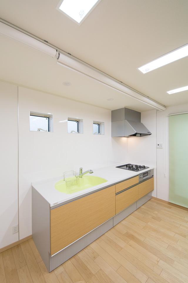 小窓を配置しさわやかなライムグリーンのシンクを使用した、明るい雰囲気のキッチン。