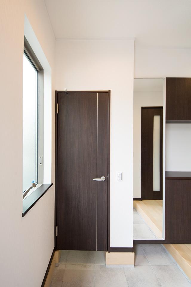 大きな縦すべり窓を設け、明るく開放感のある玄関。