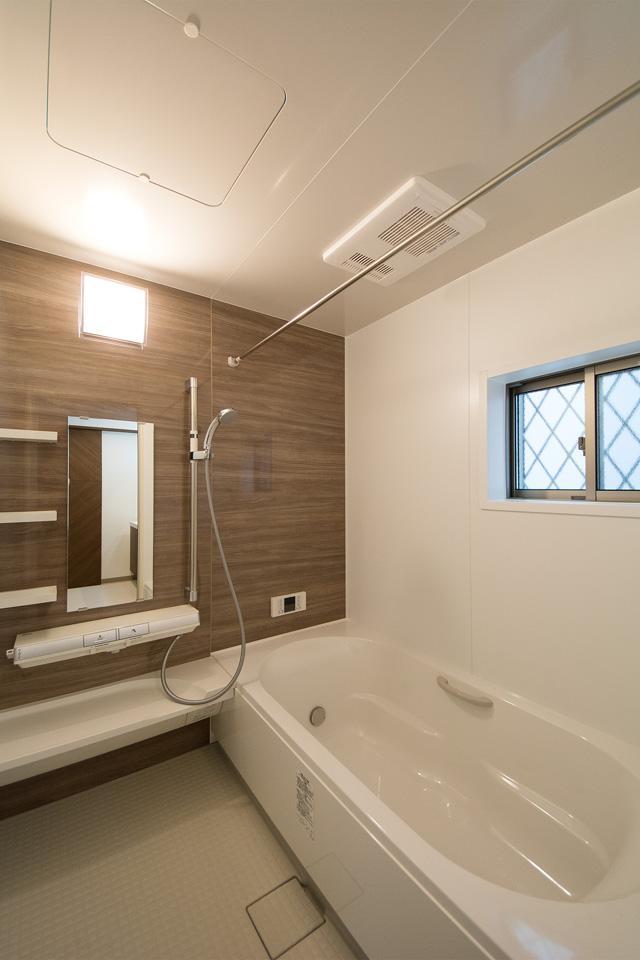 モカカラーのアクセントパネルを使用したバスルーム。くつろぎの時間を演出します。
