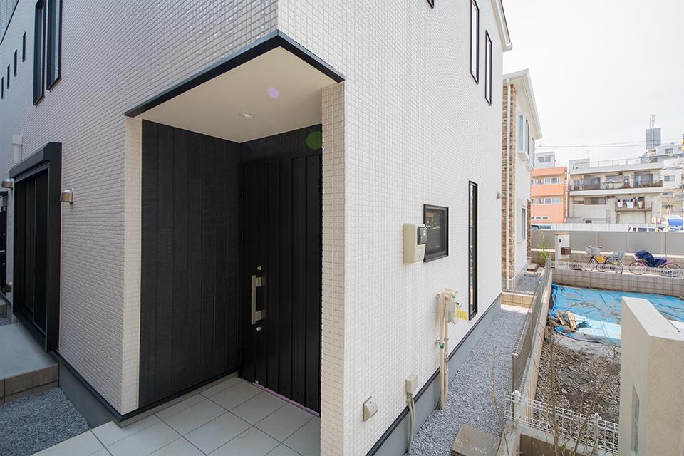 シックなカラーの玄関ドアがファサードの表情を引き締めます。