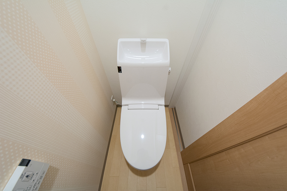 爽やかな配色のクロスで清潔感ある1階トイレ。