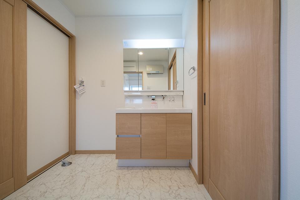 白を基調とした清潔感のあるサニタリールーム。ブラウンの洗面化粧台がナチュラルな空間を演出します。