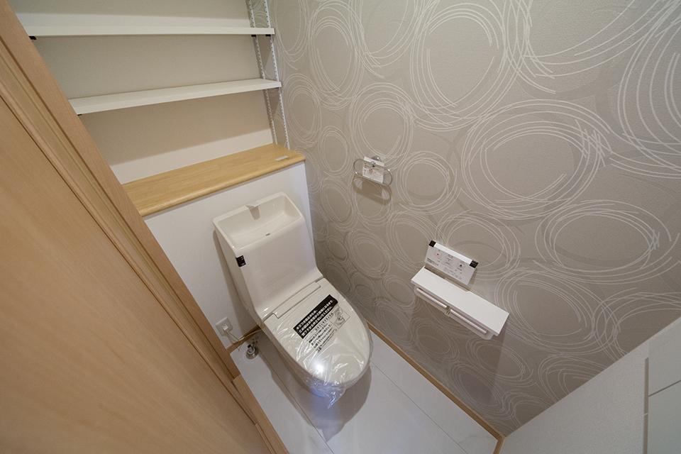 グレーのアクセントクロスが落ち着いた雰囲気を演出する1階トイレ。